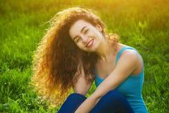 Attraktives, junges Mädchen mit dem gelockten Haar, das auf dem grünen Gras auf dem Rasen sitzt und am Fotografen lächelt Stockfotos