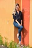 Attraktives junges Modell in der Jacke und in Jeans, die nahe Wandhintergrund aufwerfen Lizenzfreie Stockfotos
