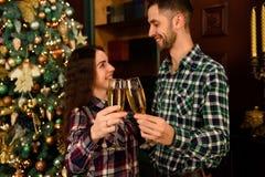Attraktives junges Paar feiert Feiertag zu Hause zusammen, trinkt Champagner und lächelt mit Bengal-Lichtern herein stockbilder