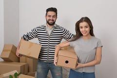 Attraktives junges Paar ist bewegend halten, lächelnd und Kästen bei der Stellung unter ungepackten Kästen lizenzfreies stockfoto