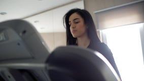 Attraktives junges sportliches Mädchen des kaukasischen Auftrittes mit langem Brunette richtet ihr Haar auf einer Tretmühle gerad stock video footage