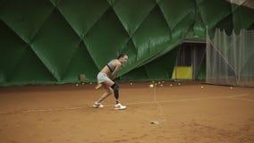 Attraktives junges Trainieren der behinderten Frau Sie tritt den Ball auf dem elastischen Band, das zurückkommt Training langsam stock footage