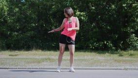 Attraktives kaukasisches Mädchen im rosa Hemd mit den Kopfhörern, die in Park tanzen Junge Frau, welche die lustigen und lächerli stock video footage