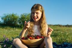 Attraktives Kindermädchen, das Erdbeere isst Naturhintergrund, grüne Wiese, Landhausstil lizenzfreies stockbild