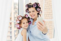 Attraktives kleines Kind mit positivem Ausdruck, bezaubernde Lächelnstände nahe ihrer Mutter, machen selfie mit modernem Handy, H stockfoto