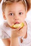 Attraktives kleines Mädchen, das Birne isst stockbild