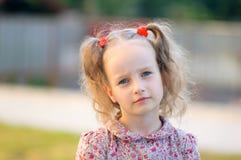 Attraktives kleines Mädchen mit blauen Augen und zwei den Pferdeschwänzen, welche die Kamera ohne Lächeln betrachten Lizenzfreies Stockfoto