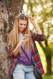 Attraktives lächelndes Mädchen, das am Handy, im Freien simst Moderne glückliche Frau mit einem Smartphone Lizenzfreie Stockbilder