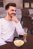Attraktives Lachen des jungen Mannes gesetzt an einer Terrasse Stockfotos