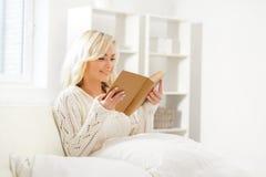 Attraktives lächelndes aufgeregtes Mädchen, das morgens ein Buch liest Stockfotografie