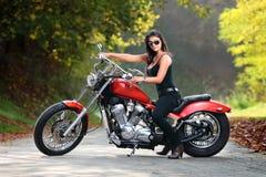 Attraktives Mädchen auf einem Motorrad, das draußen aufwirft Stockbilder