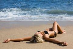 Attraktives Mädchen, das auf dem Sand durch das Meer liegt. Lizenzfreies Stockfoto