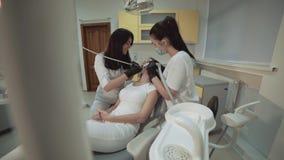 Attraktives Mädchen, das auf den Zähnen reinigen Behandlung liegt stock footage