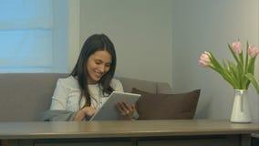 Attraktives Mädchen, das auf Sofa unter Verwendung der Berührungsfläche und des Lächelns sitzt lizenzfreies stockbild