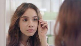 Attraktives M?dchen, das Augenbrauen auf Gesicht mit vorderem Spiegel der Pinzette am Badezimmer zupft stock video