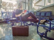 Attraktives Mädchen, das in der Halle, auf den Flug wartend sitzt dre Lizenzfreie Stockfotografie