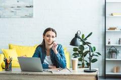 attraktives Mädchen, das durch Smartphone spricht und an der Kamera beim Studieren mit Laptop und Notizbüchern lächelt stockbilder