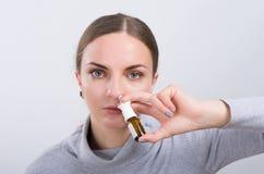 Attraktives Mädchen, das eine Medizin mit Spray innerhalb der Nase auf hellem Hintergrund einnimmt Lizenzfreie Stockfotos