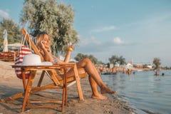 Attraktives Mädchen, das an einem Handy auf dem Strand spricht lizenzfreie stockbilder