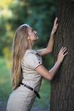 Attraktives Mädchen, das einen großen Baum im Park berührt und oben schaut Stockbild