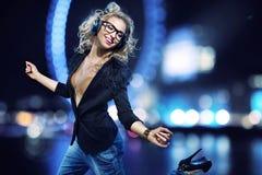 Attraktives Mädchen, das herein Musik in die Stadt hört Lizenzfreie Stockfotos