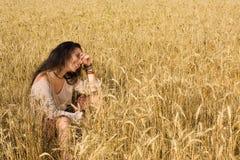 Attraktives Mädchen, das im goldenen Weizen sitzt Stockbild