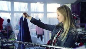 Attraktives Mädchen, das Kleidung im Mall wählt stock footage