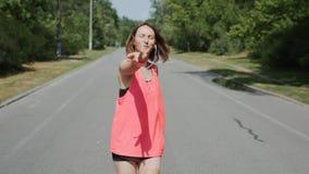 Attraktives Mädchen in den Kopfhörern, die zur Kamera im Park schauen Sportive Frau im rosa Hemd lächelnd und Spaß im Park habend stock video