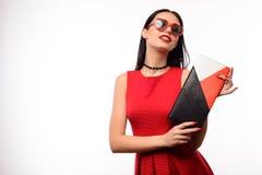 Attraktives Mädchen in einem roten Kleid und in einer tragenden Sonnenbrille in Form eines Herzens hält eine mehrfarbige Kupplung Stockbilder