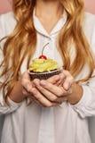 Attraktives Mädchen in einem weißen Hemd hält kleine Kuchen Stockbilder