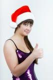 Attraktives Mädchen in einem Weihnachtshut mit dem Daumen oben Lizenzfreie Stockfotografie