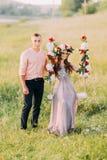 Attraktives Mädchen im Kranz, der auf Schwingen mit Blumen, Mann als Nächstes steht sie sitzt lizenzfreies stockbild