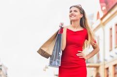 Attraktives Mädchen im roten Kleid mit Einkaufstaschen gehend die Stadtstraße Stockfotos