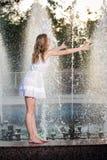 Attraktives Mädchen im weißen kurzen Kleid, das auf Geländer nahe dem Brunnen am heißesten Tag des Sommers sitzt Stockbilder