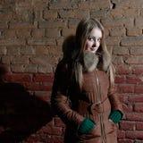 Attraktives Mädchen im Winter nahe Backsteinmauer Lizenzfreies Stockfoto