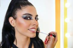 Attraktives Mädchen mit dem artsy Make-up, das Lipgloss setzt lizenzfreie stockbilder