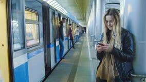 Attraktives Mädchen mit dem langen blonden Haar des Geräts in der Lederjacke richtet Stellung in der Metro gegen den Hintergrund  Lizenzfreies Stockbild