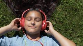 Attraktives Mädchen mit dem langen schwarzen Haar liegt auf dem Gras im Park und hört Musik auf den Kopfhörern der roten Farbe stock footage