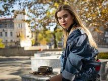 Attraktives Mädchen mit dem schönen flüssigen Haar sitzt auf einer Bank an einem schönen sonnigen Tag lizenzfreie stockbilder