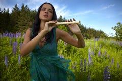 Attraktives Mädchen mit der Flöte, die auf dem Sommergebiet sitzt Stockfoto