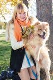 Attraktives Mädchen mit ihrem Hund, der warme Kleidung trägt Stockbild