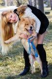 Attraktives Mädchen mit ihrem Hund, der warme Kleidung trägt Stockfotos