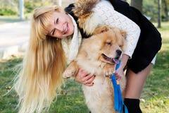 Attraktives Mädchen mit ihrem Hund, der warme Kleidung trägt Lizenzfreie Stockbilder