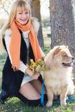 Attraktives Mädchen mit ihrem Hund, der warme Kleidung trägt Lizenzfreies Stockbild