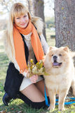 Attraktives Mädchen mit ihrem Hund, der warme Kleidung trägt Stockfotografie
