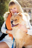 Attraktives Mädchen mit ihrem Hund, der warme Kleidung trägt Lizenzfreies Stockfoto