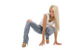 Attraktives Mädchen mit tattered Jeans sitzen auf Fußboden lizenzfreies stockbild