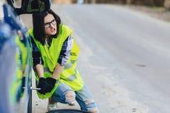 attraktives Mädchen montieren Rad vom Auto an der Straße allein ab Lizenzfreie Stockbilder