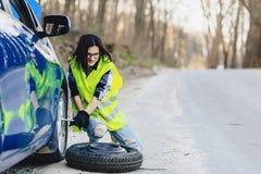 attraktives Mädchen montieren Rad vom Auto an der Straße allein ab Stockfoto