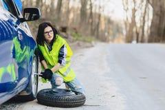attraktives Mädchen montieren Rad vom Auto an der Straße allein ab Stockbilder